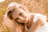 Photo sensual blonde woman touching hair while looking at camera in sunshine