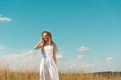 stylová blondýna žena v bílých šatech a slamák klobouk mluví na smartphone na louce proti modré obloze