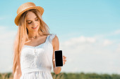 Photo blonde woman in white dress and straw hat showing smartphone with blank screen against blue sky