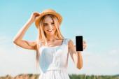 mladá blondýna žena v bílých šatech dotýkající se slaměný klobouk při zobrazení smartphone s prázdnou obrazovkou proti modré obloze