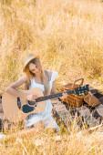 vysoký úhel pohledu blondýny v bílých šatech a slaměný klobouk hrající na akustickou kytaru na dece v poli, selektivní ostření