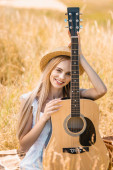 Photo selective focus of young blonde woman looking at camera while sitting with acoustic guitar in grassy field