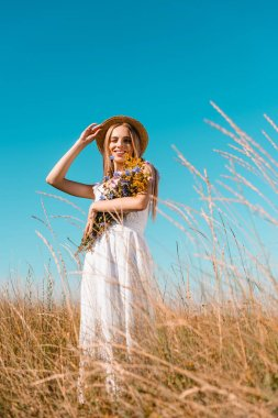Selective focus of young blonde woman in white dress holding wildflowers and touching straw hat while looking at camera stock vector