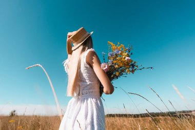 Selective focus of young woman in white dress touching straw hat while holding bouquet of wildflowers against blue sky stock vector