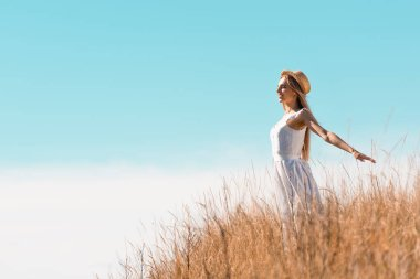 Blonde woman in straw hat and white dress standing with outstretched hands on hill against blue sky stock vector