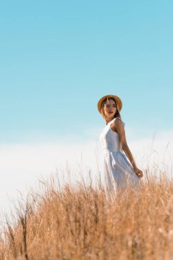 Selective focus of young woman in straw hat touching white dress while standing on grassy hill stock vector