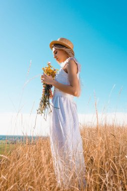 Side view of stylish woman in white dress and straw hat holding wildflowers against blue sky stock vector