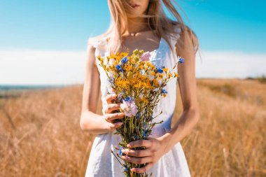 Cropped view of young woman in white dress holding wildflowers in grassy field, selective focus stock vector