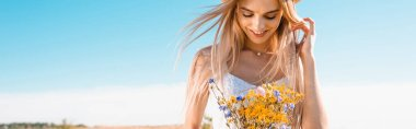 Panoramic crop of sensual blonde woman holding bouquet of wildflowers against blue sky stock vector