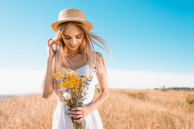 Sensual young woman in white dress and straw hat holding wildflowers and touching hair in grassy meadow stock vector