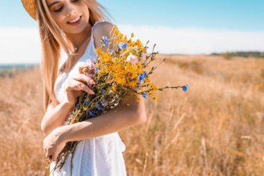 Selective focus of young blonde woman holding bouquet of wildflowers in meadow stock vector