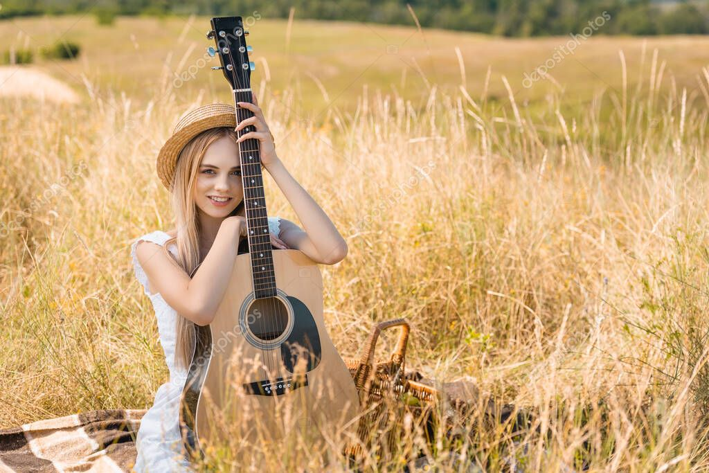 Selective focus of blonde woman in summer outfit and straw hat sitting on blanket with acoustic guitar and looking at camera stock vector