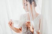 Selektivní zaměření mladé nevěsty držící krajkový závoj v blízkosti bílých záclon