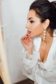 Brunette bride in silk robe and bra touching lips and looking away
