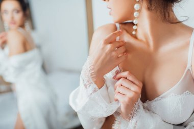 Cropped view of bride in lace bra and pearl earring touching silk robe at home