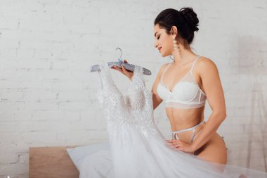 Seductive bride in lingerie and pearl earrings holding hanger with lace wedding dress on bed