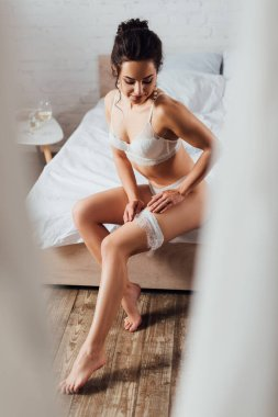 Selective focus of sexy bride in lingerie and pearl earrings putting on lace garter on bed