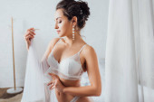 Bruneta nevěsta ve spodním prádle drží závoj doma