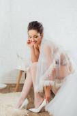 Bruneta nevěsta ve spodním prádle a závoj nosí podpatky vedle svatební šaty v ložnici