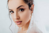 Selective focus of brunette bride in pearl earrings and veil looking at camera