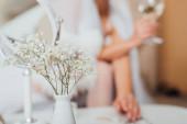 Selektiver Fokus der Blumen in der Vase und Braut mit einem Glas Wein im Hintergrund
