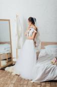 Braut in Höschen und Schleier hält Kleiderbügel mit Brautkleid in der Nähe von Spiegel und Strauß auf dem Bett