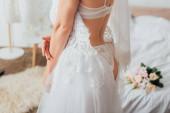 Oříznutý pohled na nevěstu ve spodním prádle a závoj uvedení na krajky svatební šaty v ložnici