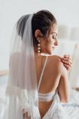 Zadní pohled na mladou nevěstu v závoji a svatební šaty dotýkat rameno doma