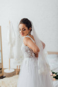 young bride in white wedding dress and lace veil at home
