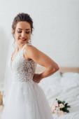 Mladá nevěsta v závoji oblékání svatební šaty doma