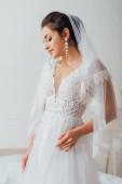 Mladá nevěsta nosí perlové náušnice, závoj a svatební šaty doma