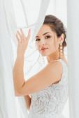 Brünette Braut im Brautkleid aus Spitze blickt in die Kamera, während sie Vorhänge berührt