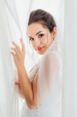 Boční pohled mladé brunetky nevěsta při pohledu na kameru při dotyku záclony doma