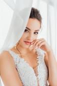 Selektivní zaměření nevěsty s rukou u rtů při pohledu na kameru poblíž bílých záclon