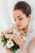Selektivní zaměření mladé nevěsty ve svatebních šatech a závoj dotýkající se květin vedle závěsů