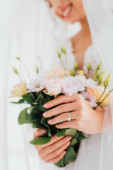 Cropped view of bride with jewelry ring on finger holding bouquet