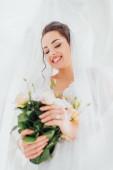 Selektivní zaměření mladé nevěsty v závoji a šaty drží květinové kytice