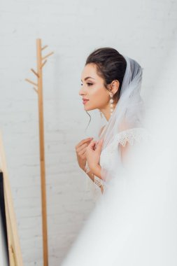 Selective focus of brunette bride in pearl earring wearing veil at home