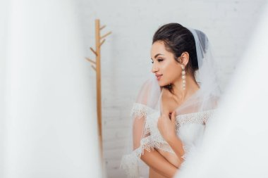 Selective focus of brunette bride in bra and pearl earring wearing lace veil and looking away at home stock vector