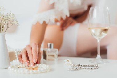 Cropped view of bride touching pearl necklace, near glass of wine and flowers on coffee table