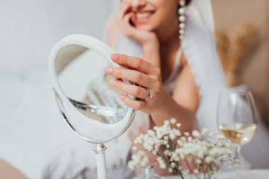 Cropped view of bride touching mirror near flowers and glass on wine stock vector