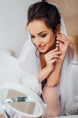 Selective focus of bride in veil looking at camera while touching pearl earring at home
