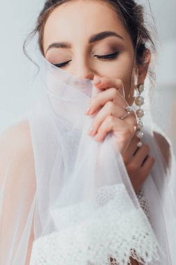 Selective focus of young bride in pearl earring touching lace veil