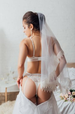 Back view of sexy bride in lingerie and lace veil wearing wedding dress in bedroom stock vector