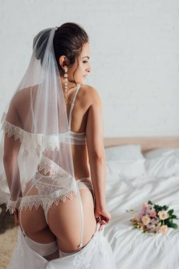 Back view of sexy bride putting on white wedding dress in bedroom