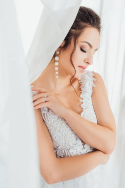 Selective focus of bride in lace dress and pearl earrings touching shoulder near curtains