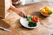 částečný pohled na mladou ženu držící okurku u talíře s brokolicí a červenou paprikou