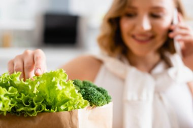 Selective focus of woman touching fresh lettuce near broccoli while talking on smartphone stock vector