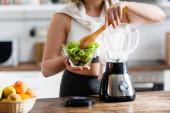 abgeschnittene Ansicht einer Frau mit Schüssel mit Salat und Kochlöffel in der Nähe des Mixers