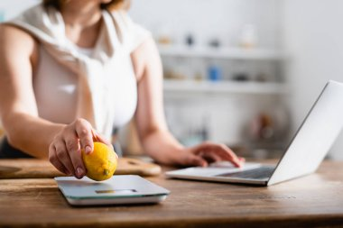 cropped view of woman putting lemon on kitchen scales and using laptop